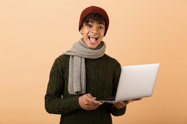 ラップトップコンピューターを保持しているベージュの壁に隔離された秋の服に身を包んだ幸せな若いアフリカ人の肖像画