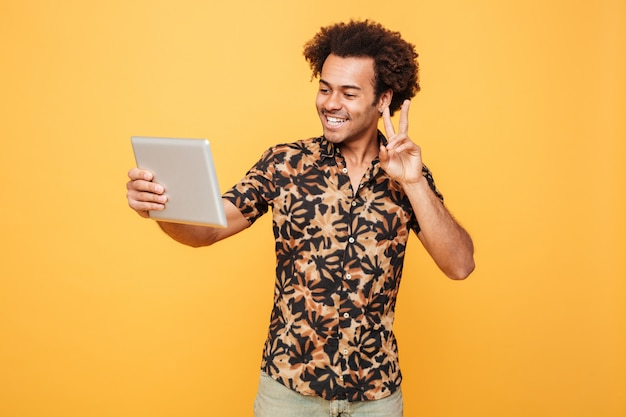 Портрет счастливого молодого африканского человека держа таблетку пк