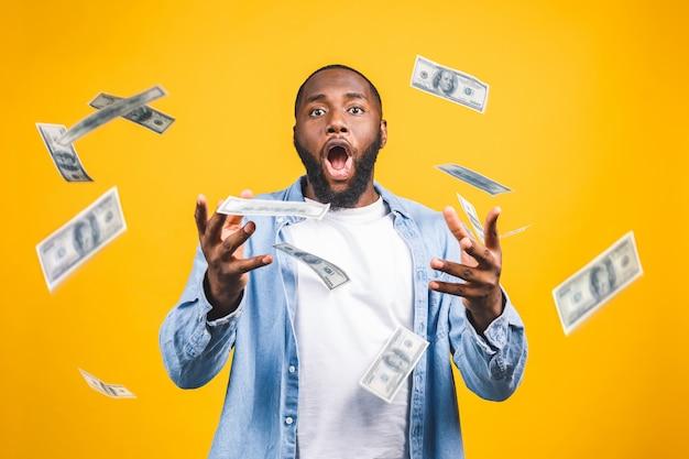 Портрет счастливого молодого афро американского человека выбрасывая деньги банкноты, изолированные на желтом фоне.