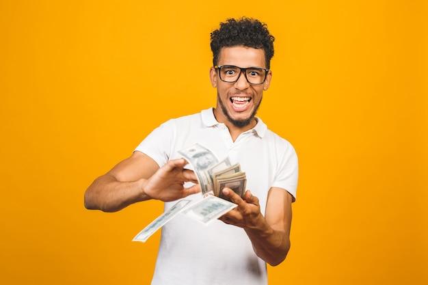 お金の紙幣を投げる幸せな若いアフロアメリカ人男性の肖像画