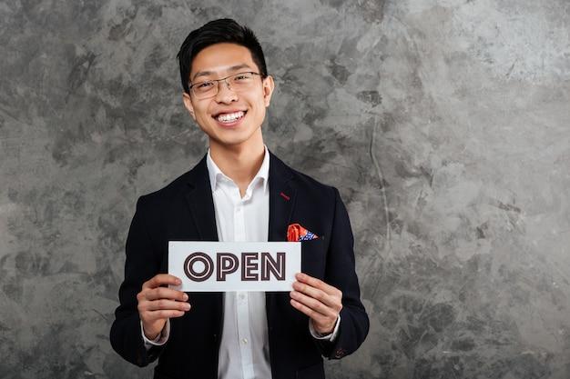 Портрет счастливого молодого азиатского человека одетого в костюме