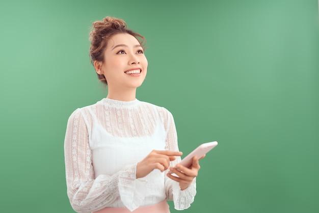 Портрет счастливой молодой азиатской женщины держа мобильный телефон стоя и смотря вверх изолированный над зеленой предпосылкой.