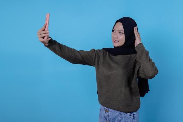 파란색 배경에 격리된 휴대전화로 행복한 젊은 아시아 여성 셀카의 초상화