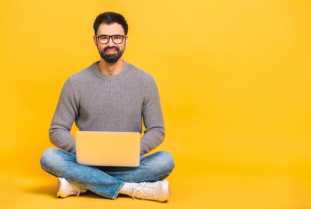 Портрет счастливого молодого бородатого человека в случайном холдинге портативный компьютер, сидя на полу, изолированном на желтом фоне.