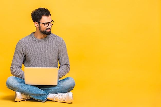 黄色の背景で隔離の床に座っている間、ラップトップコンピューターを持ってカジュアルに幸せな若いひげを生やした男の肖像画。
