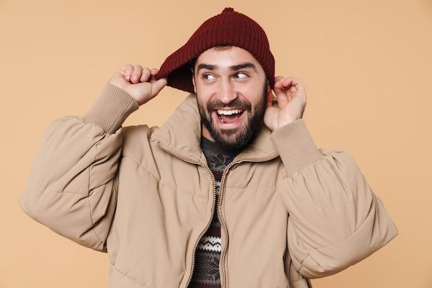 Портрет счастливого молодого бородатого мужчины в зимней куртке и шляпе, стоящего изолированно на бежевом