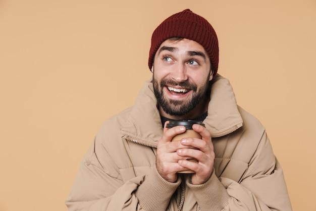 Портрет счастливого молодого бородатого мужчины в зимней куртке, стоящего изолированно на бежевом, с чашкой кофе на вынос