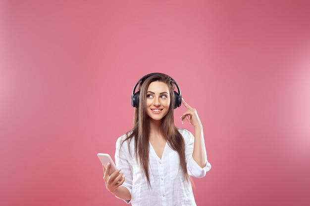 ピンクの壁に孤立してポーズをとって幸せな若い美しい女性の肖像画