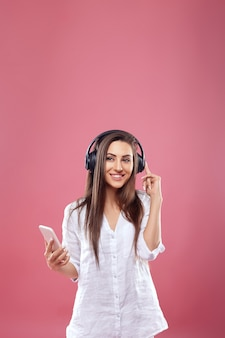 Портрет счастливой молодой красивой женщины позирует изолированной над розовой стеной