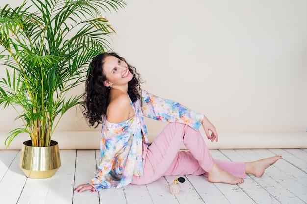 ベージュの背景のヤシの木の横にあるスタジオの床に座っているピンクのパジャマで幸せな若いブルネットの少女の肖像画