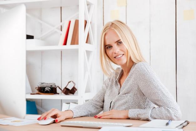 オフィスでコンピューターと座っている幸せな若いビジネス女性の肖像画