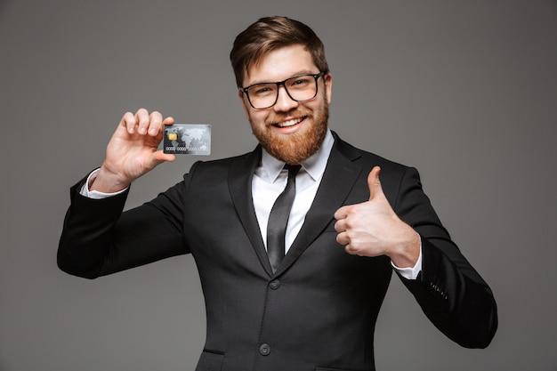 クレジットカードを保持している幸せな青年実業家の肖像画