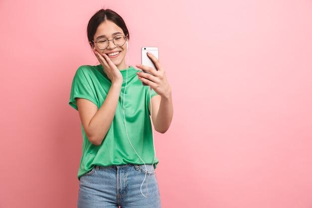 ピンクの壁に孤立して立っている幸せな若いカジュアルな女の子の肖像画、イヤホンと携帯電話でビデオ通話