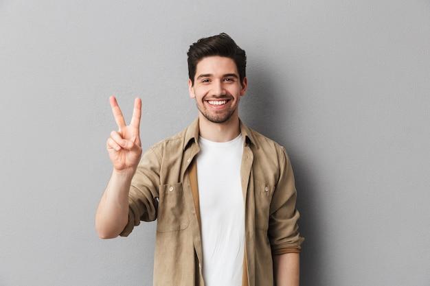 平和を示す幸せな若いカジュアルな男の肖像