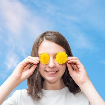 Портрет счастливой молодой кавказской девушки прикрывает глаза желтыми одуванчиками, веселится, держит в руках любимые цветы, имеет зубастую улыбку, любит свободное время на фоне голубого неба с облаками.