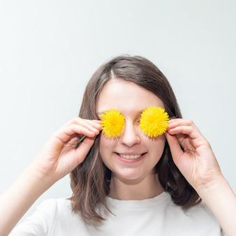 Портрет счастливой молодой кавказской девушки прикрывает глаза желтыми одуванчиками, веселится, держит в руках любимые цветы, имеет зубастую улыбку, любит свободное время. счастливый женский день концепция