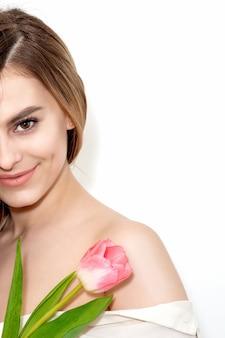 Портрет счастливой молодой кавказской женщины с одним розовым тюльпаном на белом фоне с копией пространства