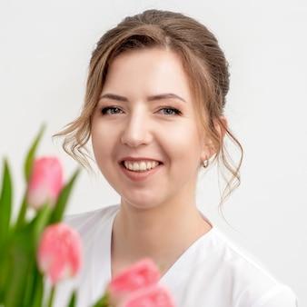 흰색 배경에 핑크 튤립과 행복 한 젊은 백인 여자의 초상화
