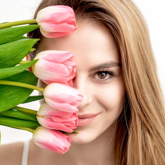 Портрет счастливой молодой кавказской женщины с розовыми тюльпанами на белом фоне