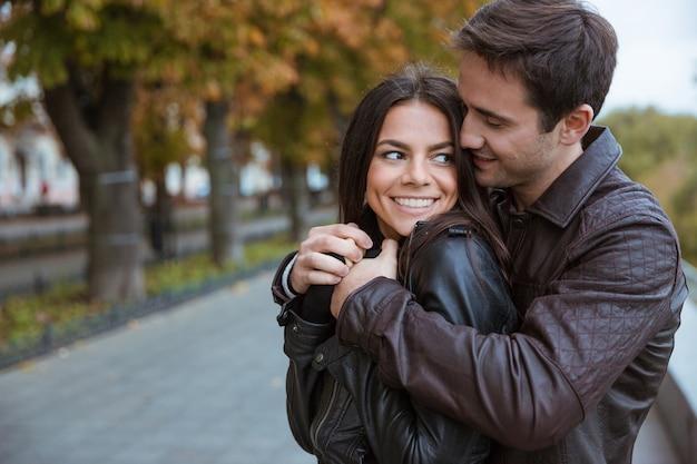 秋の公園でいちゃつく幸せな若いカップルの肖像画