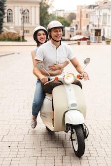 街の通りで一緒にバイクに乗ってヘルメットをかぶった幸せな若いカップルの肖像画