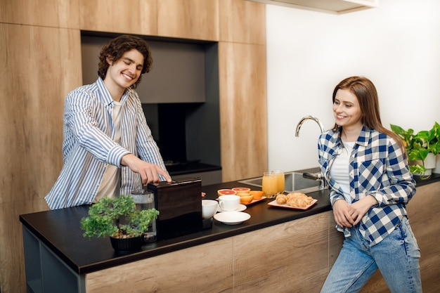 キッチンのテーブルでおいしい朝食をしながらコーヒーマシンを使用して恋に幸せな若いカップルの肖像画。