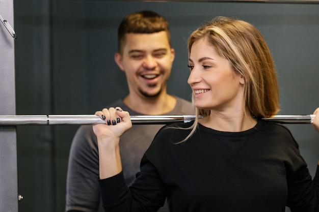몇 가지 무게를 해제 하 고 체육관에서 함께 운동 스포티 한 복장에 행복 한 젊은 커플의 초상화. 스포티 한 체육관 개념.
