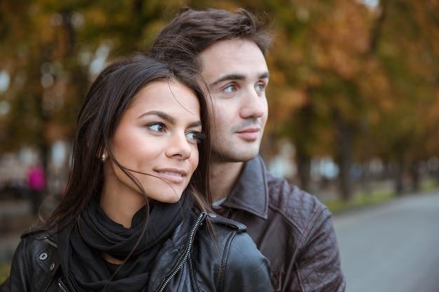 屋外で目をそらしている幸せな若いカップルの肖像画