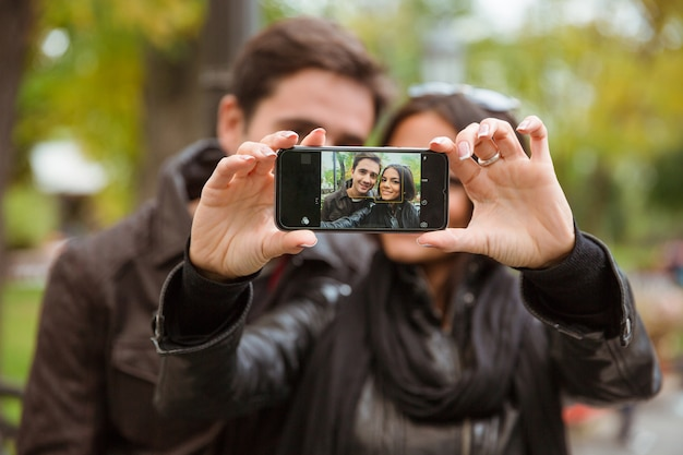 屋外のスマートフォンで自分撮り写真を作る幸せな若いカップルの肖像画。スマートフォンの画面に焦点を当てる
