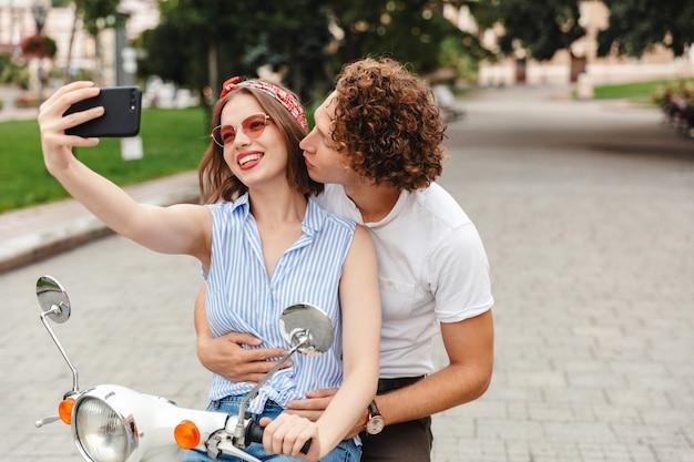 Портрет счастливой молодой пары, вместе едущей на мотоцикле по городской улице, делающей селфи, целующейся
