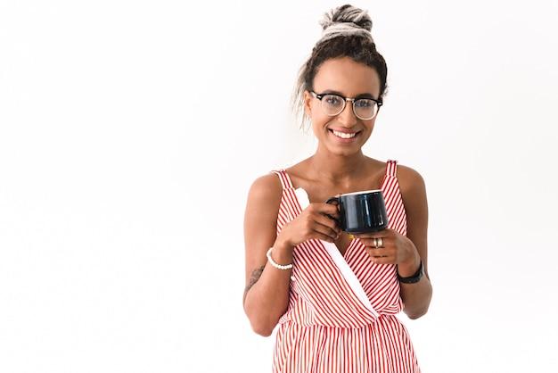 Портрет счастливой молодой милой жизнерадостной женщины с боится представлять изолированный на белом питьевой кофе или чай.