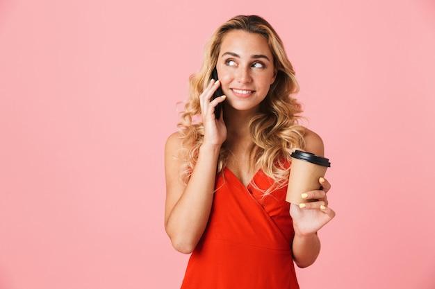 Портрет счастливой молодой возбужденной милой белокурой женщины, позирующей изолированной над розовой стеной, разговаривающей по мобильному телефону, пьющей кофе.
