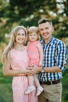 夏の日の休暇で自然に一緒に時間を過ごす幸せな若い家族の肖像画。日没時に公園を歩いたり遊んだりする父、母、少女。閉じる。