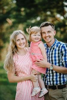 自然、休暇、屋外で一緒に時間を過ごす幸せな若い家族の肖像画。ママ、パパ、娘は緑の芝生に立っています。家族の休日の概念。
