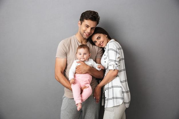 彼らの小さな女の赤ちゃんと幸せな若い家族の肖像画