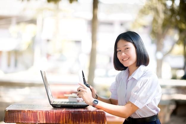 음악과 노트북으로 야외에서 휴식을 취하는 행복한 젊은 여학생의 초상화