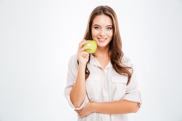 Портрет счастливой молодой девушки, держащей зеленое яблоко, изолированное на белой стене
