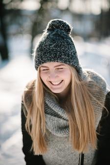 ジャンプして冬の公園で雪を楽しんで幸せな若い女の子の肖像画。