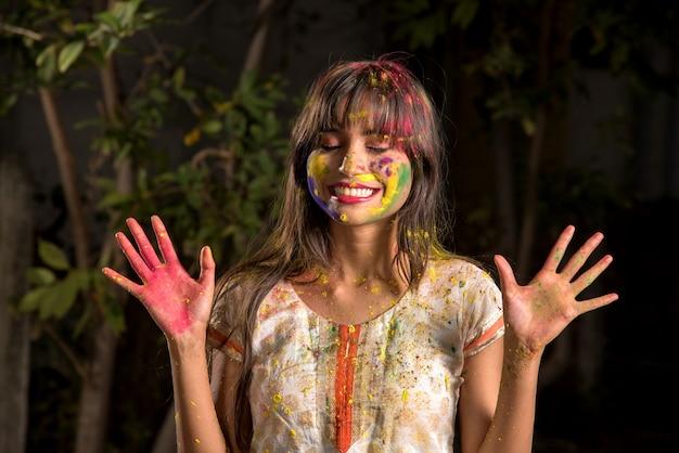 색상 holi의 축제에 행복 한 젊은 여자의 초상화. 포즈와 색상의 축제를 축하하는 소녀.