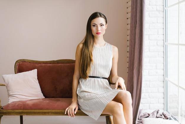 家の窓のソファに座っている幸せな少女の肖像画。彼女の唇に赤い口紅、家のガラス窓の上に休んでいる若い美しいセクシーな女性の肖像画。