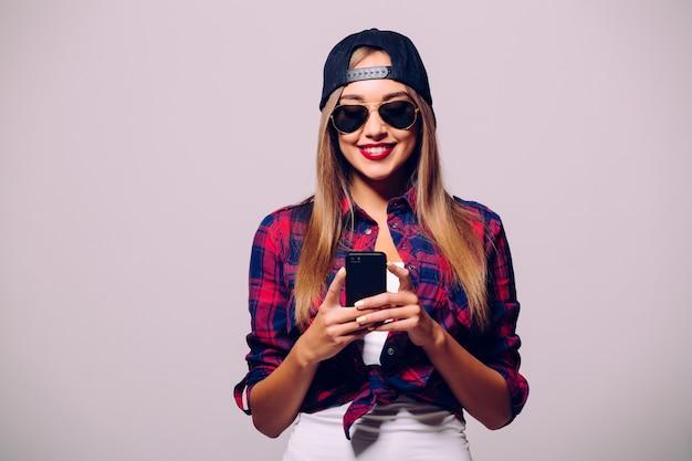 회색 벽에 고립 된 스마트 폰을 사용하여 행복 한 어린 소녀의 초상화