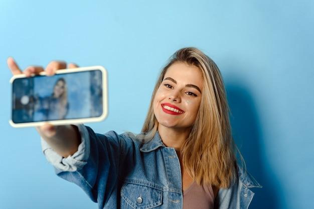 Портрет счастливой молодой девушки с блеском на щеках, делающей селфи, изолированным на синем фоне. изображение возбужденной счастливой молодой женщины, делающей селфи с камерой.