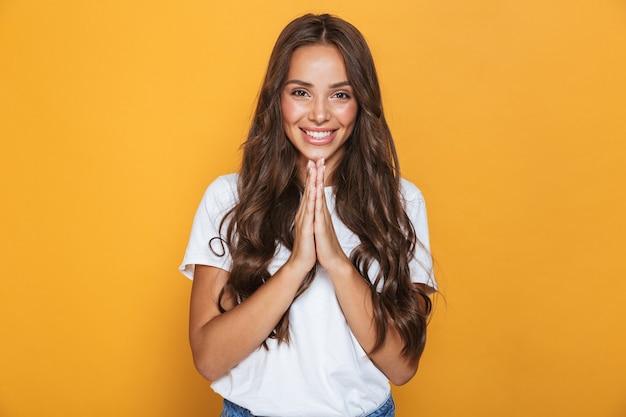 黄色の壁の上に立って、物乞いの長いブルネットの髪を持つ幸せな少女の肖像画 Premium写真