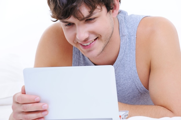 ノートパソコンで幸せな若い男の肖像画