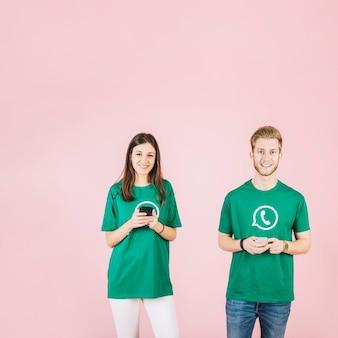 분홍색 배경 앞에 핸드폰을 들고 행복 한 젊은 남자와 여자의 초상화