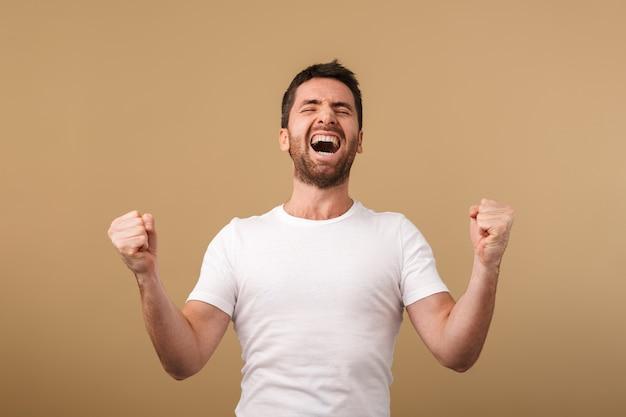 Портрет счастливого молодого человека, небрежно одетого, стоящего изолированно над бежевым, празднуя успех