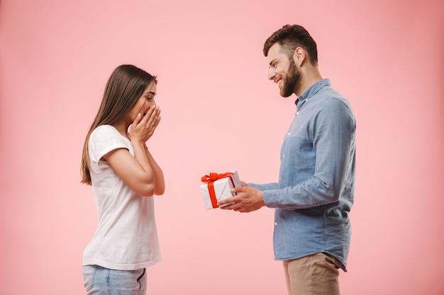 彼のガールフレンドを与える幸せな若い男の肖像