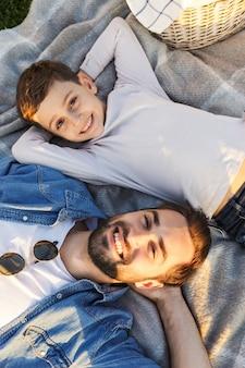 公園の嘘で彼の弟や息子のoutoorsと楽しんで幸せな若い男の肖像画