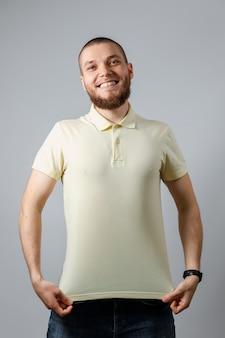 Портрет счастливого молодого человека в желтой футболке mocap на сером цвете.