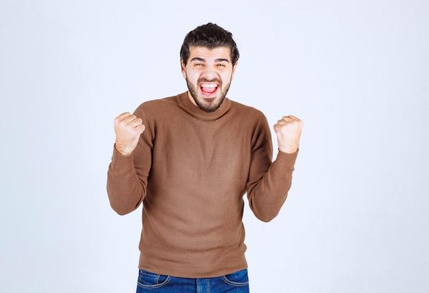 成功したポーズで幸せな若い男のモデルの肖像画。
